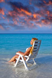 Young pretty woman in a beach chair at ocean Stock Images