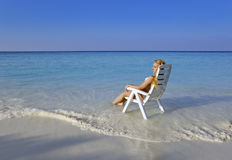 Young pretty woman in a beach chair in sea Royalty Free Stock Image