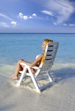 Young pretty woman in a beach chair in sea Royalty Free Stock Photo