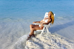 Young pretty woman in a beach chair in sea Stock Image
