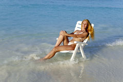 Young pretty woman in a beach chair in sea Royalty Free Stock Photos