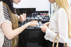 Young pretty woman and beauty consultant in shop Stock Photography