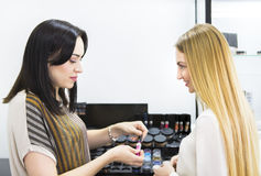 Young pretty woman and beauty consultant in shop Stock Photos