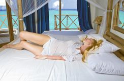 Young pretty woman in bed with ocean behind window Royalty Free Stock Photography