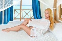 Young pretty woman in bed with ocean behind window Stock Image