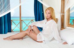 Young pretty woman in bed with ocean behind window Stock Photography