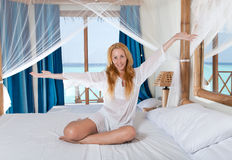 Young pretty woman in bed with sea behind window. Stock Photo