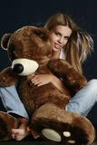 Young pretty woman with big teddy bear. Posing in studio royalty free stock photo