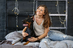 Young pretty woman with black doberman dog Stock Photos
