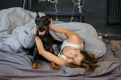 Young pretty woman with black doberman dog Royalty Free Stock Photo