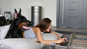 Young pretty woman with black doberman dog. Lying in the bed stock footage