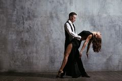 Young pretty woman in black dress and man dance tango. Young pretty women in black dress and men dance tango, training class Stock Images