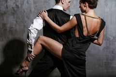 Young pretty woman in black dress and man dance tango. Young pretty women in black dress and men dance tango, training class Stock Image