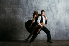 Young pretty woman in black dress and man dance tango. Young pretty women in black dress and men dance tango, training class studio Royalty Free Stock Image