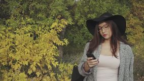 Young pretty woman in black hat and glasses typing sms to her boyfriend outdoor. Young pretty woman in black hat and glasses typing sms to her boyfriend using stock footage
