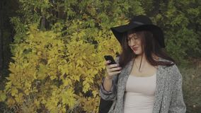 Young pretty woman in black hat and glasses using her smartphone to make selfie. Outdoor stock footage