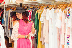 Young pretty woman in black hat trying on new dress in clothing Stock Photos