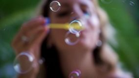 Young pretty woman blowing bubbles stock footage