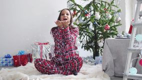 Young pretty woman blowing confetti by fir-christmas tree sits on a rug and the window in studio. slow motion. 3840x2160. Young pretty woman blowing confetti by stock footage