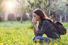 Woman blowing nose because of spring pollen allergy. Young pretty woman blowing nose in grassland with spring flowers. Pollen allergy symptoms stock photography