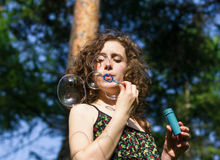 Young pretty woman blowing soap bubbles Royalty Free Stock Images