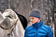 Young pretty woman in a blue jacket and a sports hat for a walk with a white horse. In the winter birch forest royalty free stock photo