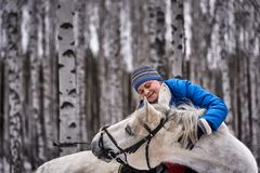 Young pretty woman in a blue jacket and a sports hat for a walk with a white horse. In the winter birch forest royalty free stock images