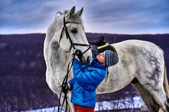 Young pretty woman in a blue jacket and a sports hat for a walk with a white horse. In the winter cloudy day stock photos
