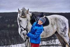 Young pretty woman in a blue jacket and a sports hat for a walk with a white horse. In the winter cloudy day stock photography