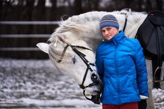 Young pretty woman in blue jacket and sports hat on a walk with a white horse on a winter cloudy day. A horse licks its hands to its owner royalty free stock photography