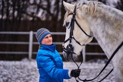 Young pretty woman in blue jacket and sports hat on a walk with a white horse on a winter cloudy day. A horse licks its hands to its owner stock images