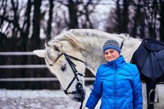 Young pretty woman in blue jacket and sports hat on a walk with a white horse on a winter cloudy day. Woman smiles stock images