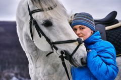 Young pretty woman in a blue jacket and a sports hat for a walk with a white horse. In the winter cloudy day royalty free stock images