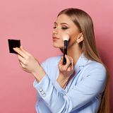 Woman with makeup brush and mirror. Young pretty woman in blue suit holding makeup brush and small mirror and applying cosmetics. Make-up artist. Girl with long Royalty Free Stock Photography