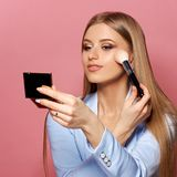 Woman with makeup brush and mirror. Young pretty woman in blue suit holding makeup brush and small mirror and applying cosmetics. Make-up artist. Girl with long Royalty Free Stock Photo