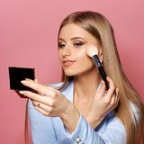 Woman with makeup brush and mirror. Young pretty woman in blue suit holding makeup brush and small mirror and applying cosmetics. Make-up artist. Girl with long Stock Image