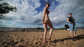 Young pretty woman in bra and underpants is dancing on summer beach near river. Young pretty woman with sunglasses, dressed in pink swimming bra and underpants stock footage