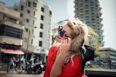 Young pretty woman in bright red dress and sunglass sits on on the bench. On the background of cityscape. Elegant blonde girl with beautiful smile on her face Stock Photos