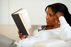 Young pretty woman browsing a book Royalty Free Stock Photos