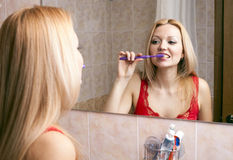Young pretty woman brushing her teeth Stock Image