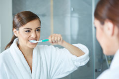Young pretty woman brushing teeth Stock Image