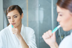 Young pretty woman brushing teeth Royalty Free Stock Photography
