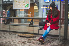 Young pretty woman on bus stop Stock Photography