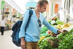 Young woman buying vegetables on market. Young pretty woman buying vegetables on market royalty free stock photography