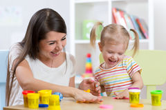 Young pretty woman and child girl playing with colorful clay in nursery Stock Images