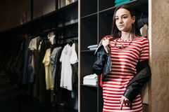The young pretty woman choosing, trying and buys dresses at shop clothing. Banner for online store clothing stock photos