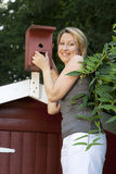 Young pretty woman controls birdhouse Royalty Free Stock Photo