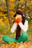 Young pretty woman with cup in the autumn park Stock Photo