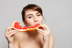 Young pretty woman or cute girl with long hair holds grapefruit fruit slice Royalty Free Stock Image