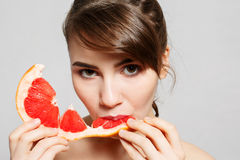 Young pretty woman or cute girl with long hair holds grapefruit fruit slice Royalty Free Stock Photos